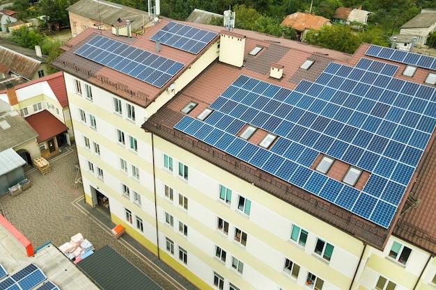 Vista aérea de la planta de energía solar con paneles fotovoltaicos azules montados en el techo del edificio de apartamentos