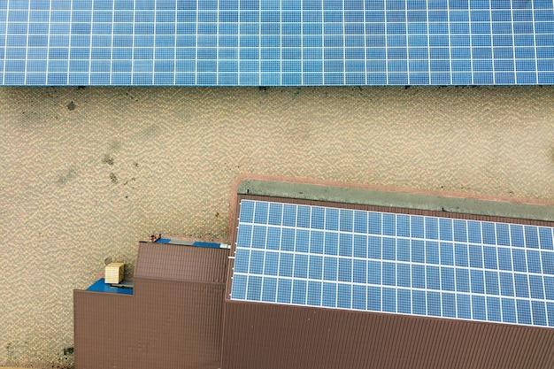 Vista aérea de la planta de energía solar con paneles fotovoltaicos azules montados en el techo del edificio industrial.