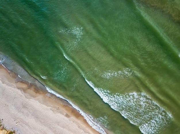 Vista aérea de playa de arena y mar con olas