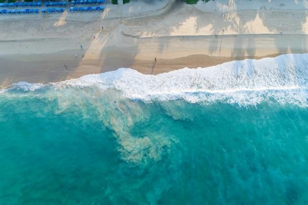 Vista aérea playa de arena y olas hermoso mar tropical en la mañana imagen de temporada de verano por vista aérea drone shot, vista de ángulo alto de arriba hacia abajo.
