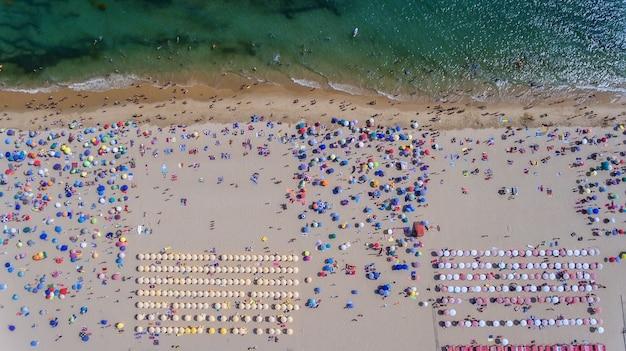 Vista aérea de la playa de arena con turistas nadando en agua de mar hermosa