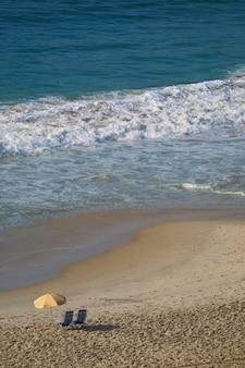 Vista aérea de la playa de copacabana con un par de sillas de playa y sombrilla.