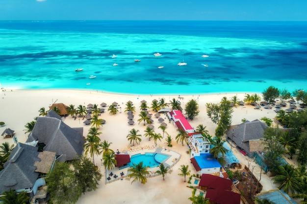 Vista aérea de la playa tropical de arena con palmeras y sombrillas en un día soleado
