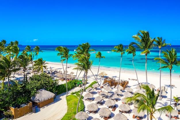 Vista aérea de la playa tropical del caribe con sombrillas de paja, palmeras y barcos. bávaro, punta cana, república dominicana