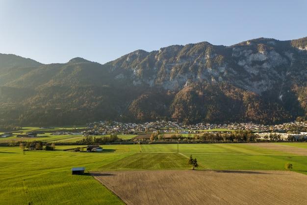 Vista aérea de prados verdes con pueblos y bosques en las montañas de los alpes austríacos.
