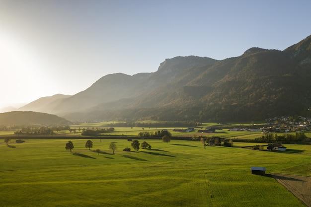 Vista aérea de prados verdes con pueblos y bosques en las montañas de los alpes.