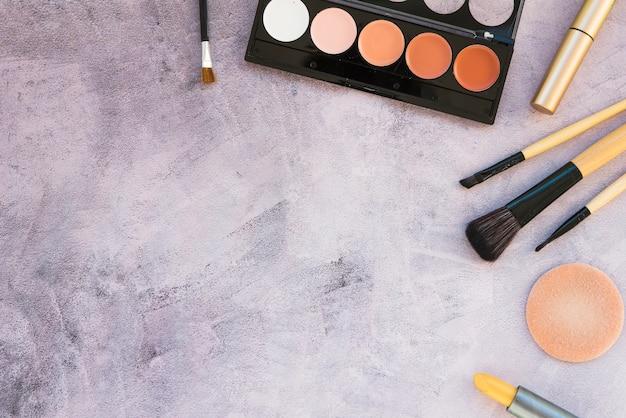 Una vista aérea de productos de belleza para maquillaje profesional sobre fondo de hormigón.