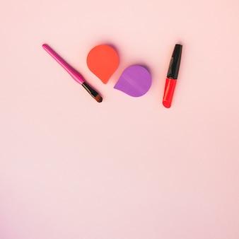 Una vista aérea de productos cosméticos sobre fondo coloreado.