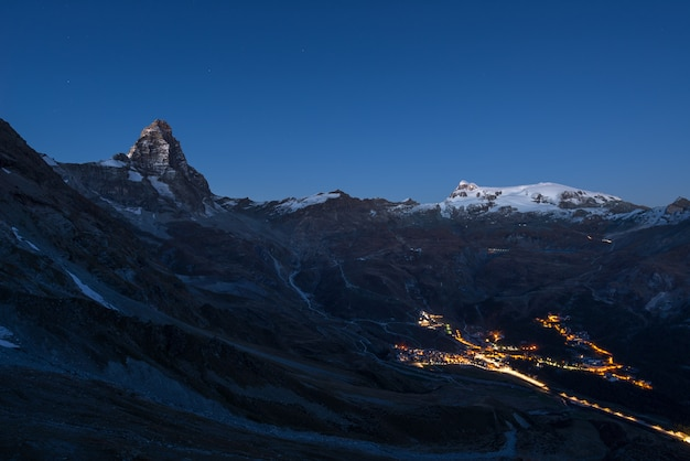 Vista aérea del pueblo de breuil cervinia brillando en la noche, famosa estación de esquí en el valle de aosta, italia. maravilloso cielo estrellado sobre el pico de la montaña matterhorn (cervino) y los glaciares monte rosa.
