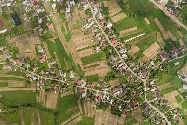 Vista aérea del pueblo con hileras de edificios y calles curvas entre campos verdes