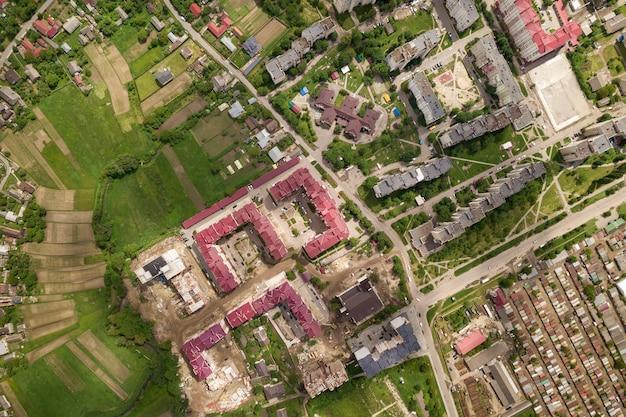 Vista aérea del pueblo o ciudad con hileras de edificios y calles con curvas en verano. paisaje urbano desde arriba.