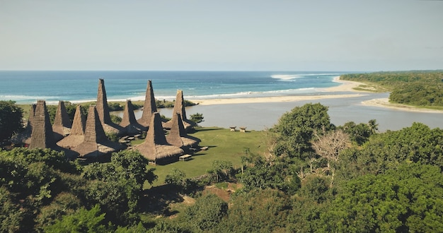 Vista aérea del pueblo tradicional con techo de casas ornamentadas en la orilla del mar de la playa de arena con árboles y plantas tropicales