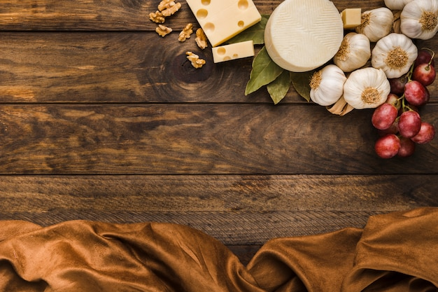 Vista aérea de queso e ingredientes con tela marrón sobre un escritorio de madera desgastado