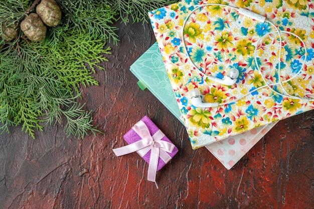 Vista aérea de ramas de abeto regalo de color púrpura y dos libros sobre fondo rojo.