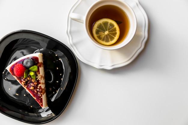 Una vista aérea de la rebanada de pastel y taza de té de limón sobre fondo blanco