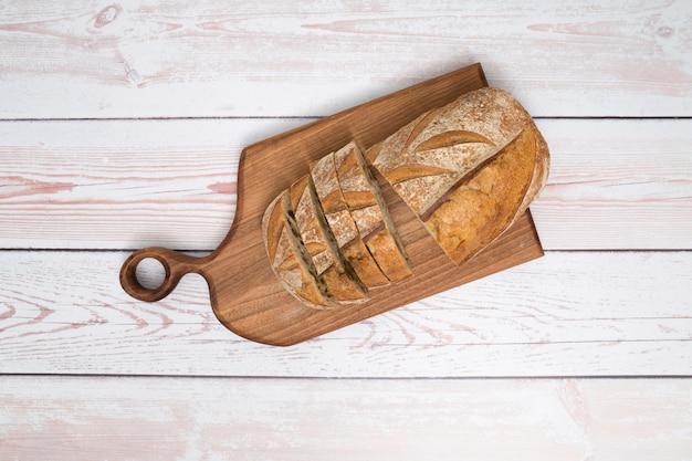 Una vista aérea rebanadas de pan en la tabla de cortar sobre el fondo de tablones de madera