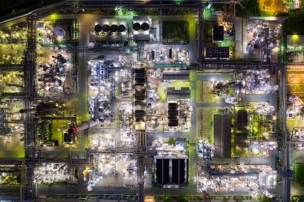 Vista aérea refinería de petróleo y planta de refinería de gas forman zona industrial en la noche.