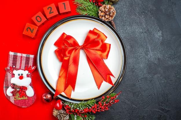 Vista aérea del regalo con cinta en el plato de cena, accesorios de decoración, ramas de abeto y números, calcetín de navidad en una servilleta roja sobre un fondo negro