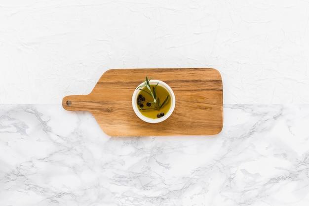 Vista aérea de romero y aceite de pimienta negra en el recipiente en el tablero de servir
