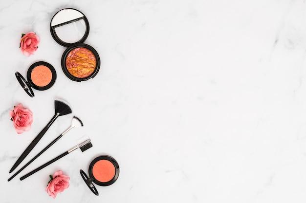 Vista aérea de rosas con polvos compactos para el rostro y pinceles de maquillaje sobre fondo blanco