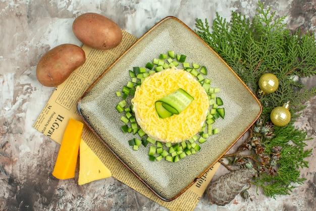 Vista aérea de sabrosa ensalada servida con pepino picado en un periódico viejo y dos tipos de patatas con queso y zanahorias sobre fondo de colores mezclados