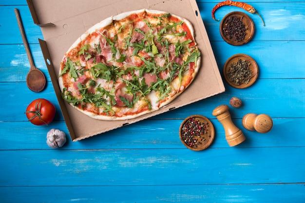 Vista aérea de sabrosa pizza con ingredientes en mesa de madera azul