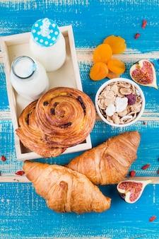 Vista aérea de sabrosos alimentos horneados; botellas de leche en la bandeja cerca de un tazón de cereal; albaricoque seco y rodajas de higo.