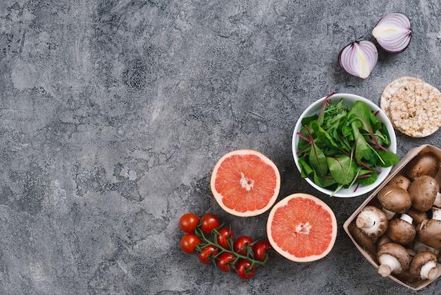 Una vista aérea de setas; rodaja de pomelo; cebolla; espinacas; tomates cherry y pastel de arroz inflado sobre fondo gris con textura