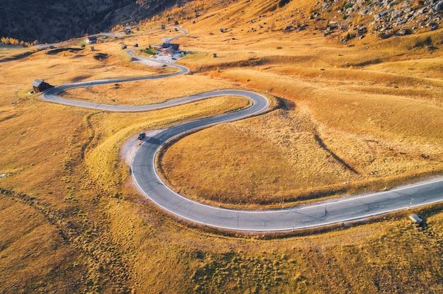 Vista aérea de la sinuosa carretera en el bosque de otoño al atardecer en las montañas