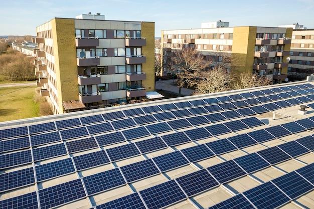 Vista aérea del sistema de paneles fotovoltaicos solares brillantes azules en el techo comercial que produce energía limpia renovable en el fondo del paisaje de la ciudad.