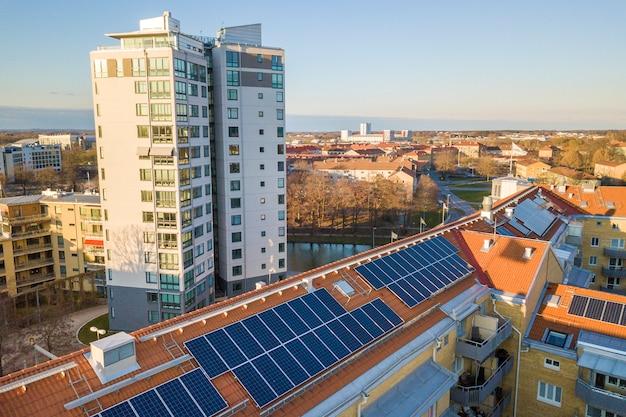 Vista aérea del sistema de paneles fotovoltaicos solares en el techo del edificio de apartamentos. concepto de producción de energía verde ecológica renovable.