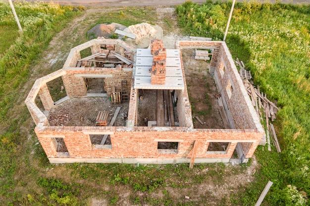 Vista aérea del sitio de construcción para la futura casa, piso de sótano de ladrillo y pilas de ladrillo para la construcción.