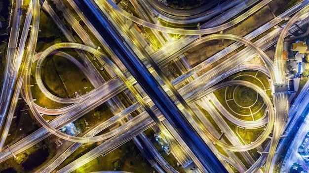 La vista aérea sobre el camino de la intersección complica y la manera expresa en la noche.