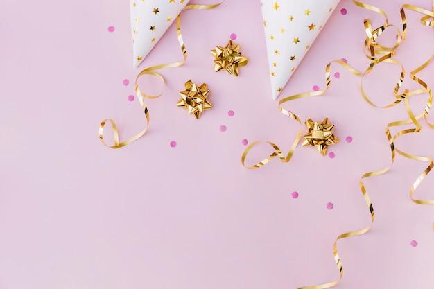 Una vista aérea del sombrero de papel blanco; espolvorear; arco dorado y serpentina sobre fondo rosa