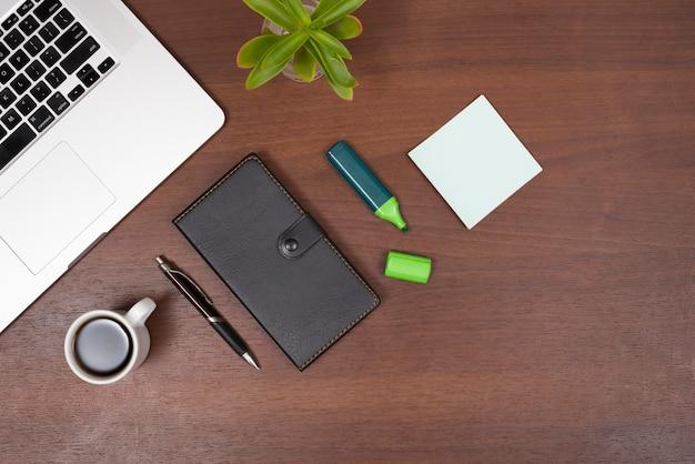 Vista aérea de suministros de oficina; té; planta y laptop en escritorio de madera