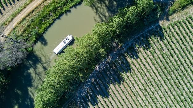 Vista aérea superior del barco en canal du midi desde arriba, viajes familiares en barcaza y vacaciones en el sur de francia