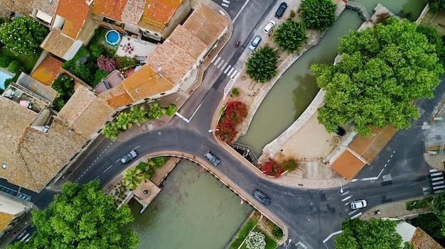 Vista aérea superior de barcos y cerradura en canal du midi, carretera y puente desde arriba, sur de francia