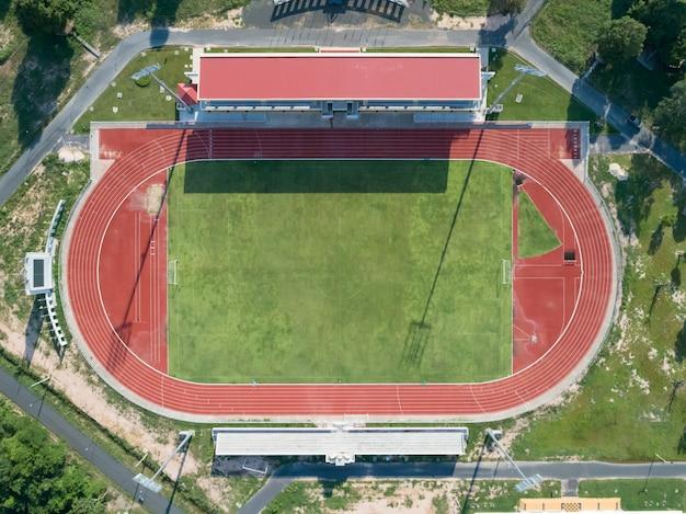 Vista aérea superior en un campo de fútbol, tribuna, campo de fútbol con pista de atletismo roja.