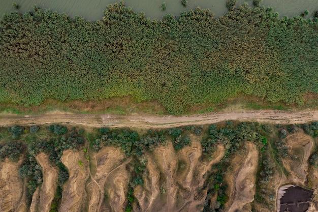 Vista aérea superior de la carretera de campo que divide grinery y dunas de arena. textura de plantas verdes vista desde arriba.