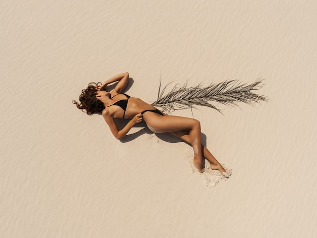 Vista aérea superior drone de mujer en traje de baño bikini relajante y tomar el sol en la playa