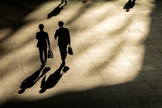 Vista aérea superior del empresario caminar y sostener maletín en tiempo de trabajo en peatones con luces y sombras.