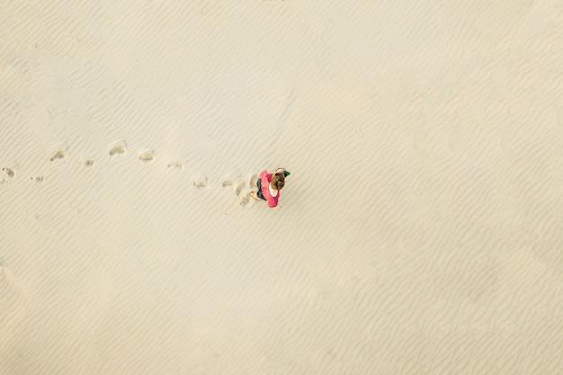 Vista aérea superior del joven solitario caminar en el desierto en la textura de la arena. concepto perdido