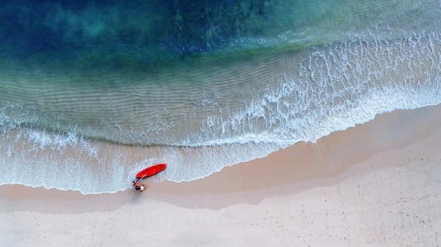 Vista aérea superior de kayak alrededor del mar con sombra de agua azul esmeralda y espuma de ola