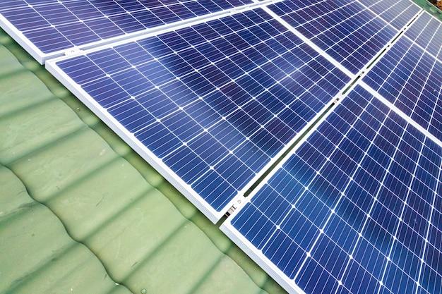Vista aérea superior de la nueva casa residencial moderna casa de campo con azul brillante sistema de paneles fotovoltaicos solares en el techo
