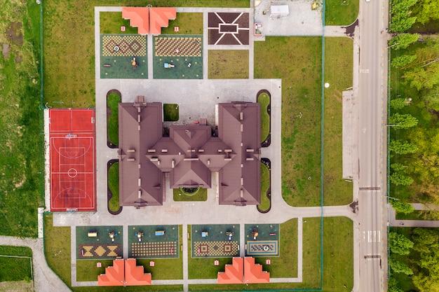 Vista aérea superior del nuevo edificio preescolar y patio con huecos y césped verde.