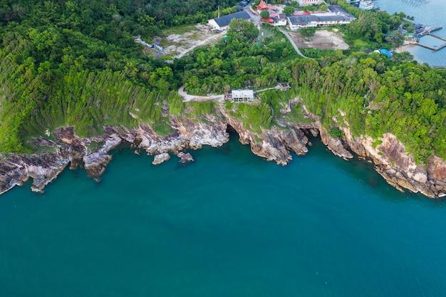 Vista aérea superior de las olas del mar, playa y costa rocosa y hermoso bosque.