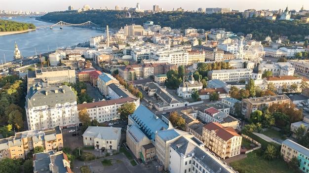 Vista aérea superior del paisaje urbano de kiev, el río dnieper y el horizonte del distrito histórico de podol desde arriba, la plaza kontraktova con rueda de la fortuna, la ciudad de kiev, ucrania