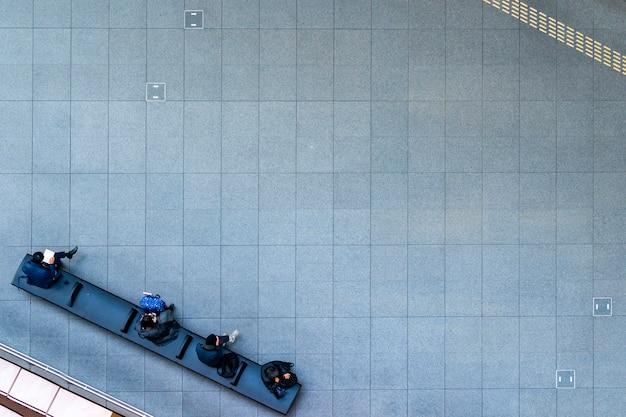 Vista aérea superior personas sentadas en el banco en la pasarela peatonal con fondo de hormigón peatonal, concepto de naturaleza muerta social con tecnología y estilo de vida
