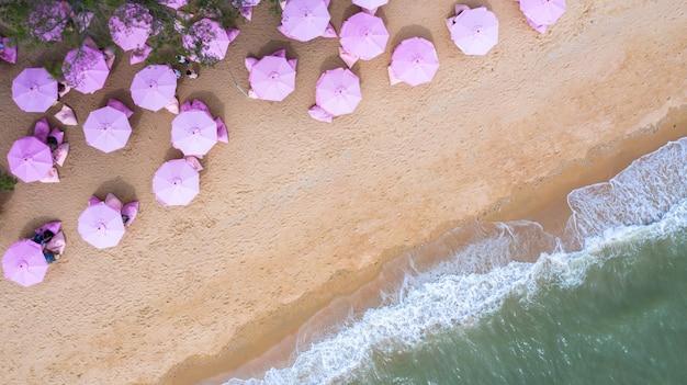 Vista aérea superior en la playa de arena. sombrillas rosas
