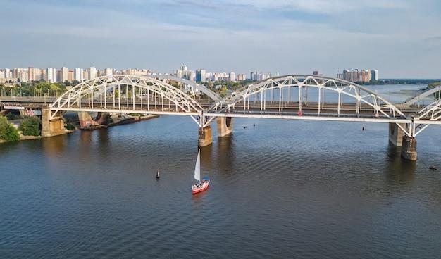 Vista aérea superior del puente darnitsky, yates y barcos que navegan en el río dnieper